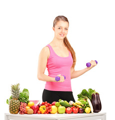 Smiling woman holding weights and table full of fruits and veget