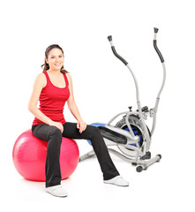 Female resting on a pilates ball next to a cross trainer
