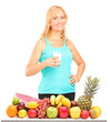 Woman holding a glass of milk with pile of fruits on a table