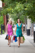 Shopaholic Female Friends Walking On Sidewalk