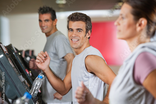 Men And Woman Running On Treadmill
