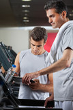 Instructor Making Notes While Standing Besides Man On Treadmill