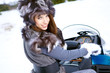 Smiling young woman riding a snowmobile
