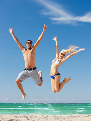 happy couple jumping on the beach