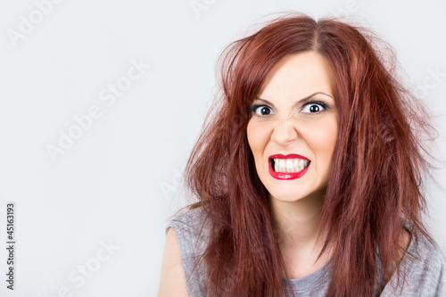 Angry unkempt redhead with red lipstick on white background