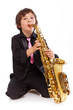 Portrait of handsome kid posing in studio with saxophone