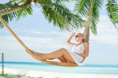 view of nice young lady swinging  in hummock on tropical beach