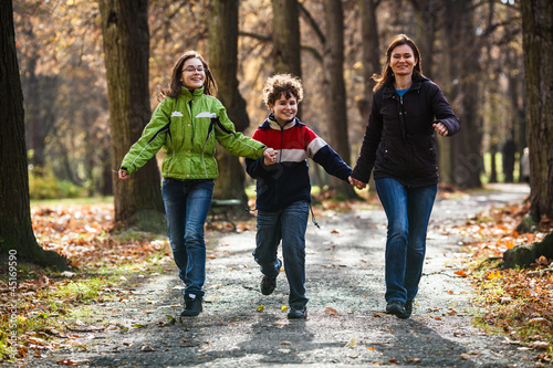 Active family - mother and kids walking, running outdoor