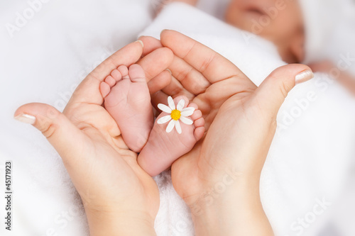 Lovely infant foot with little white daisy - 45171923