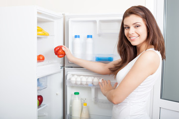 Woman taking pepper from fridge