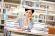 Woman surrounded with piles of books reads sitting at the desk