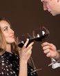 Young happy couple enjoying a glasses of red wine