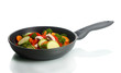 frying pan with vegetables on white
