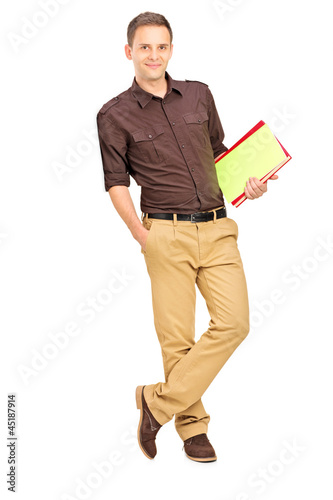 Smiling student leaning against wall