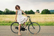 Pretty young woman relaxing with bike in a country road.