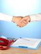 shaking hands after signing the agreement, on a blue background