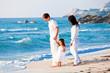 glückliche junge familie mit kleiner Tochter am Strand am wasse