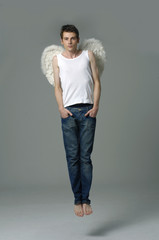 young male angel in a studio .jumping