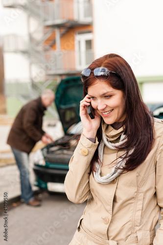 Woman on the phone repairman fixing car
