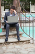 Young Businessman with Computer next to Swimming Pool