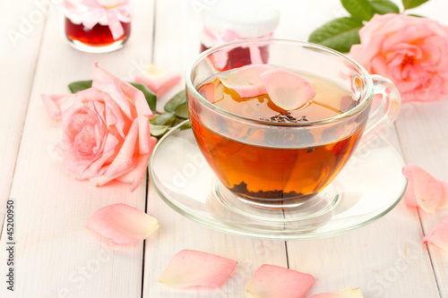 cup of tea with roses and jam on white wooden table