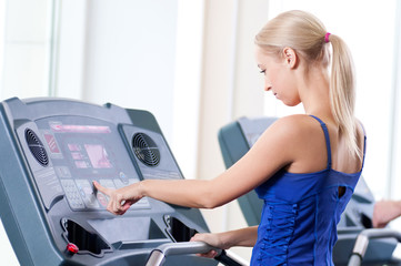 Two young women run on machine in the gym