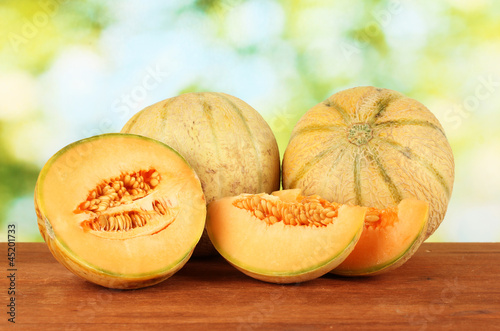 Cut melon on wooden table on green background