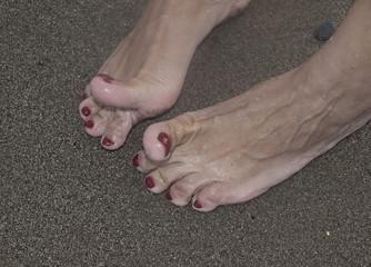 Pies desnudos con uñas rojas