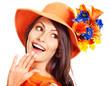 Happy woman wearing orange hat with flower.