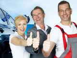 Team of car mechanics show thumbs up for good teamwork