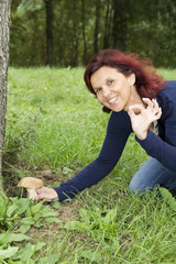 Happy woman has found a mushroom and showing OK sign