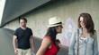 Three people walking along wall with graffiti, steadicam shot