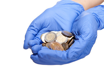 Human hands in medical gloves holding coins