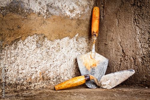 Masonry trowels on a concrete wall