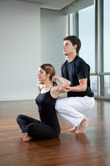 Yoga Instructor Assisting Woman
