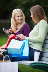 Women With Shopping Bags Using Tablet PC Outdoors
