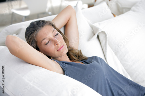 Young beautiful woman sleeping on white couch