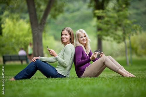 Female Friends With Cellphones In Park