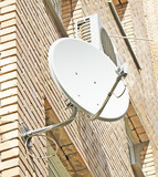 Satellite dish mounted on a brick wall