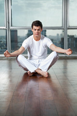 Young Man Meditating On Wooden Floor