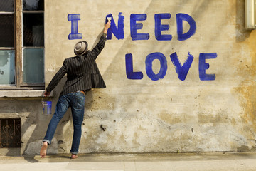 young boy writing on a wall: I need love