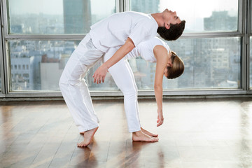 Male Yoga Instructor Assisting Woman