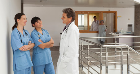Doctor and two nurses discoursing in a hospital