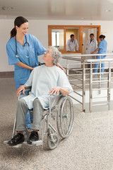 Nurse laughing with old women sitting in wheelchair
