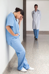 Sad nurse leans against wall