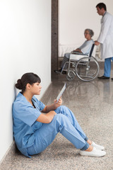 Nurse reading sitting on floor