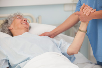 Elderly patient holding hand of nurse