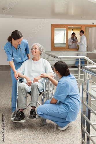 Old woman in wheelchair talking with nurses