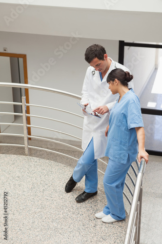 Nurse and doctor standing in the hallway and discussing