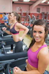 Women running on a treadmill in a gym smiling
